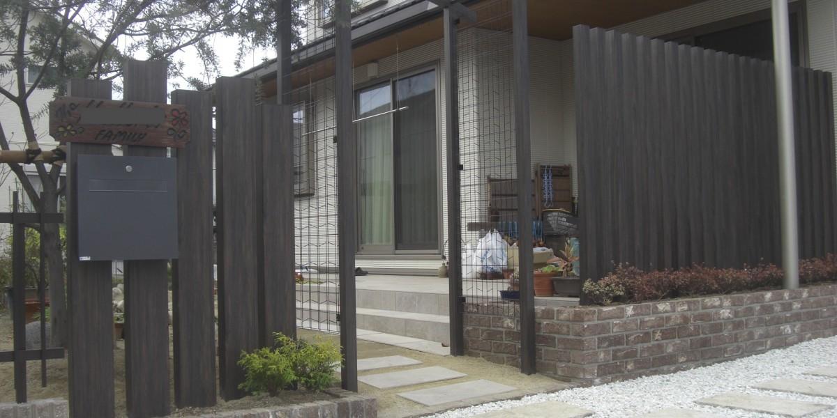 木目調アルミ柱材のスリットフェンスとレンガ積み花壇・タイルデッキの施工例