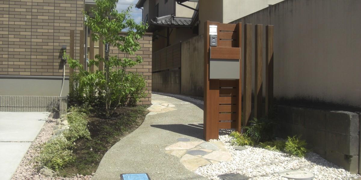 ナチュラルな印象の木目調の門柱と洗い出しアプローチの新築外構施工例